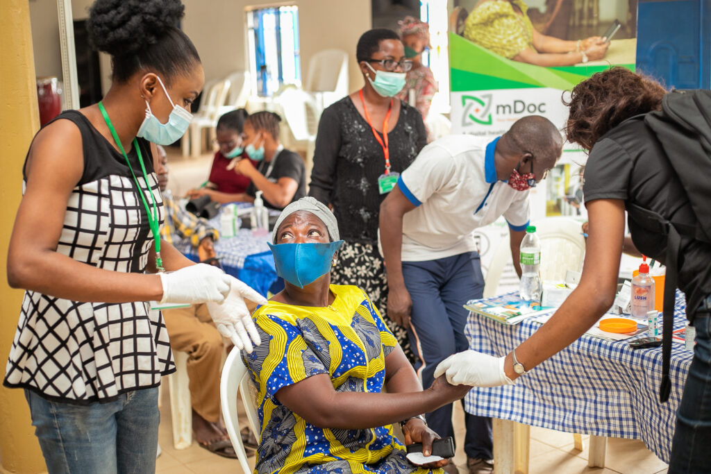 mDoc roving health coaches at a community screening event for chronic disease in Nigeria. Photo courtesy of mDoc Healthcare.